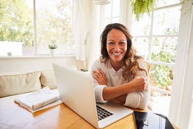 Portrait of a woman laughing while sitting at a table in her living room working from home using a tablet and laptop