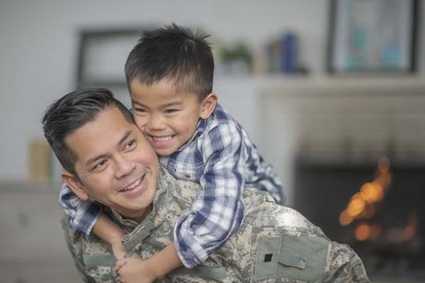 A military dad and his son are hugging in their living room. The son is smiling happily at the camera.