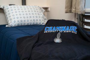 Chaminade University shirt on bed in student dorm at Hale Lokelani