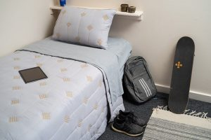 Bed in student residence hall at Chaminade University Hale Lokelani