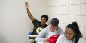 sociology student with hand raised in classroom at Chaminade